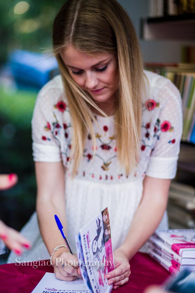 Lili firmando Todos tenemos un lado (oscuro) rosa